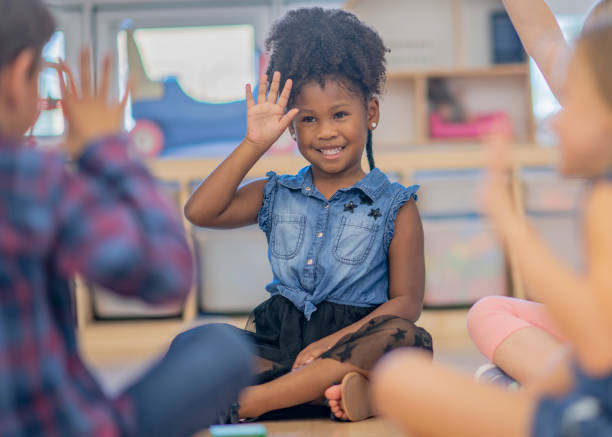 children waving in kindergarten class - sign language stock photos and pictures