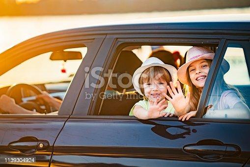 972962180istockphoto Children waving through car window 1139304924