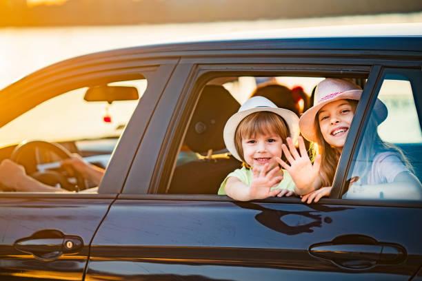enfants agitant par la fenêtre de voiture - homme faire coucou voiture photos et images de collection