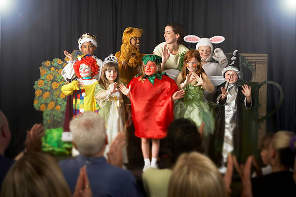 Children (4-9) wearing costumes and teacher waving on stage  performance stock pictures, royalty-free photos & images