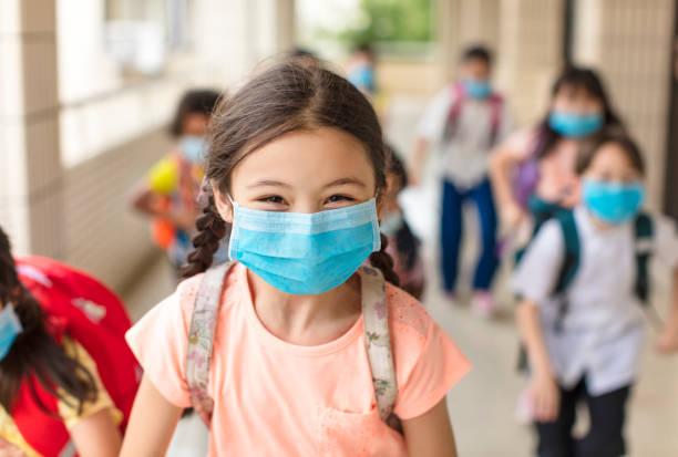 barn bär ansiktsmedicinsk mask tillbaka till skolan efter covid-19 karantän - 6 7 år bildbanksfoton och bilder