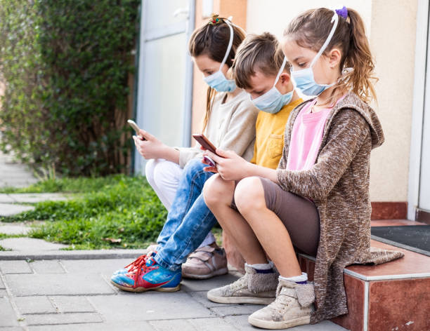 Children wearing protective mask and playing with mobile phones stock photo