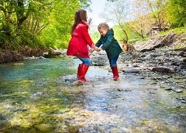 children wearing rain boots jumping into a mountain river - kinder winterstiefel stock-fotos und bilder
