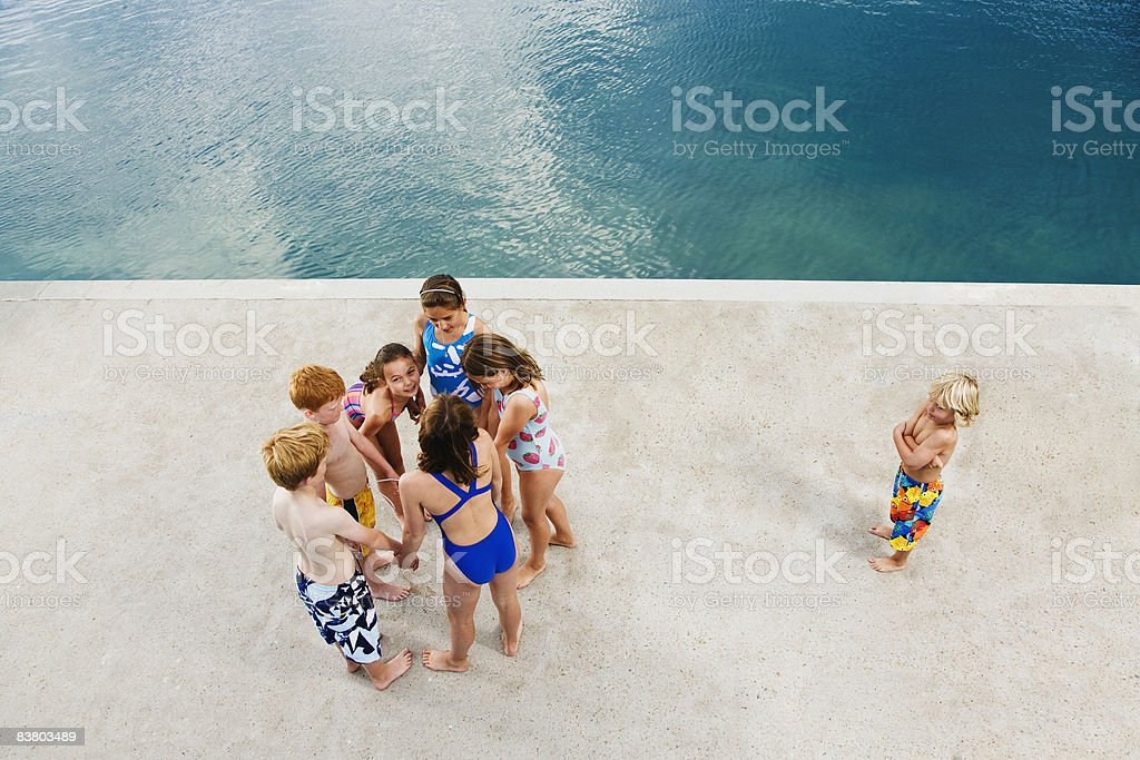 Children whispering together with one left out  royalty-free stock photo