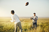 Shot of father and son playing football on an open field