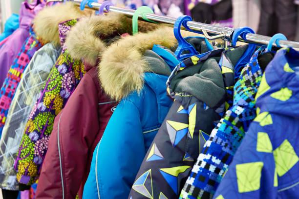 Children winter jackets on hanger in store - foto stock