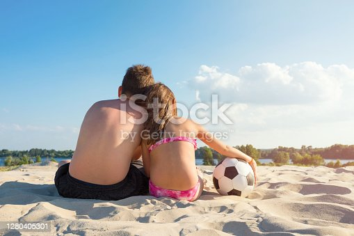 Children with a ball on the river bank on a sunny summer day. View from the back. The concept of sports and active games in the summer.