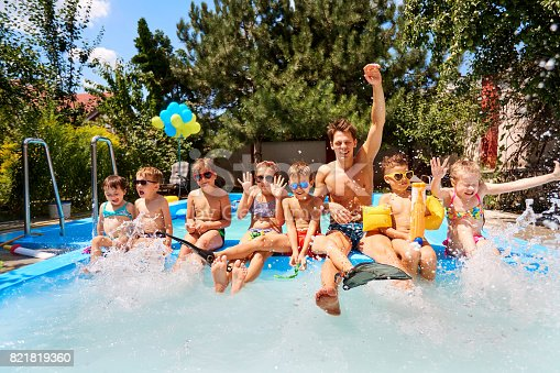 istock Children with a educator in pool in the summer camp. 821819360