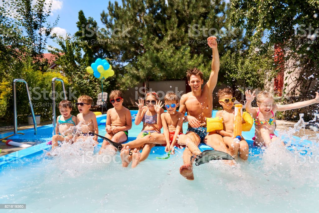 Children with a educator in pool in the summer camp. stock photo