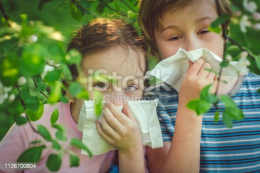 629307146istockphoto Children with allergy in spring park cleaning noses 1126700804