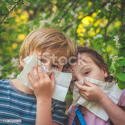 629307146istockphoto Children with allergy in spring park cleaning noses 1126700969