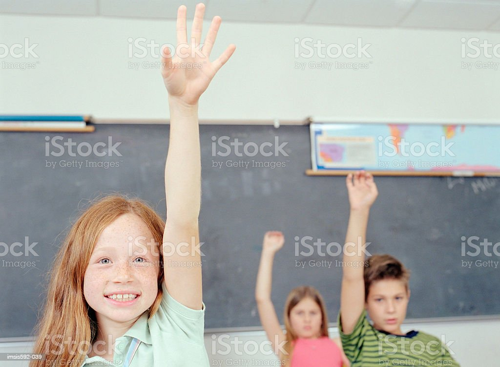 Children with arms raised in classroom royalty-free stock photo