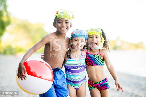 A multi-ethnic group of children on a beach in their swimsuits with snorkel gear playing with a beach ball.