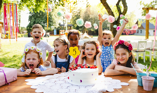 A portrait of children with cake standing around table on birthday party in garden in summer.