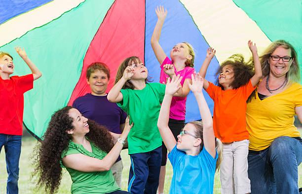betreuer im kinder camp farbenfrohen parachute - tanz camp stock-fotos und bilder