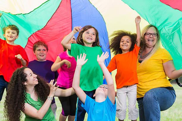 betreuer im kinder camp farbenfrohen parachute - kinderparty spiele stock-fotos und bilder