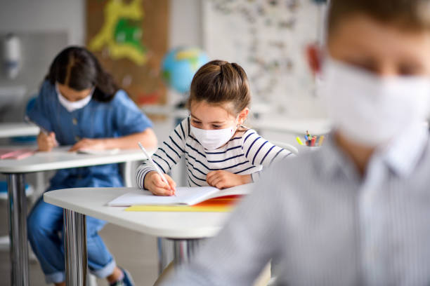 Children with face mask back at school after covid-19 quarantine and lockdown. Small children with face mask back at school after covid-19 quarantine and lockdown, writing. school building stock pictures, royalty-free photos & images
