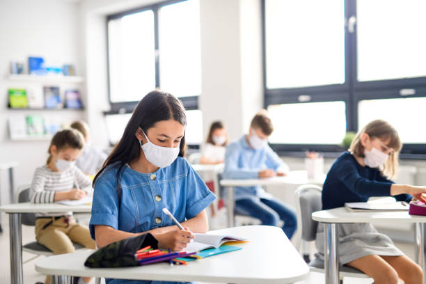 Children with face mask back at school after covid-19 quarantine and lockdown. stock photo