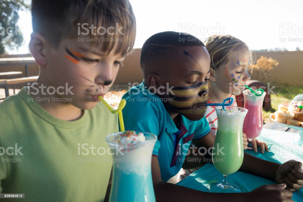 Children with face paint having drinks stock photo