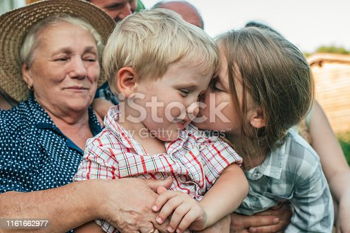 Senior woman with grandchildren near their house