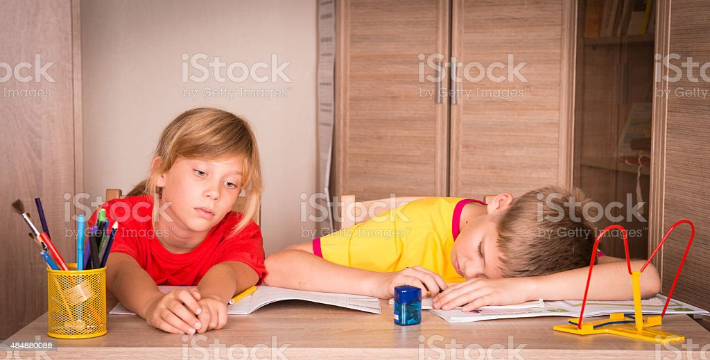 Children with learning difficulties. Tired boy and bored girl studying. stock photo
