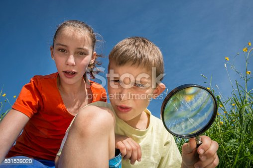 istock children with magnifying lens exploring the nature outdoors 531539020