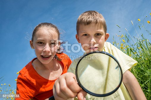 istock children with magnifying lens exploring the nature outdoors 531539134
