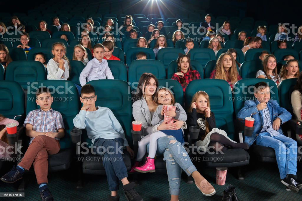 Children with parents enjoying a movie together at the cinema stock photo