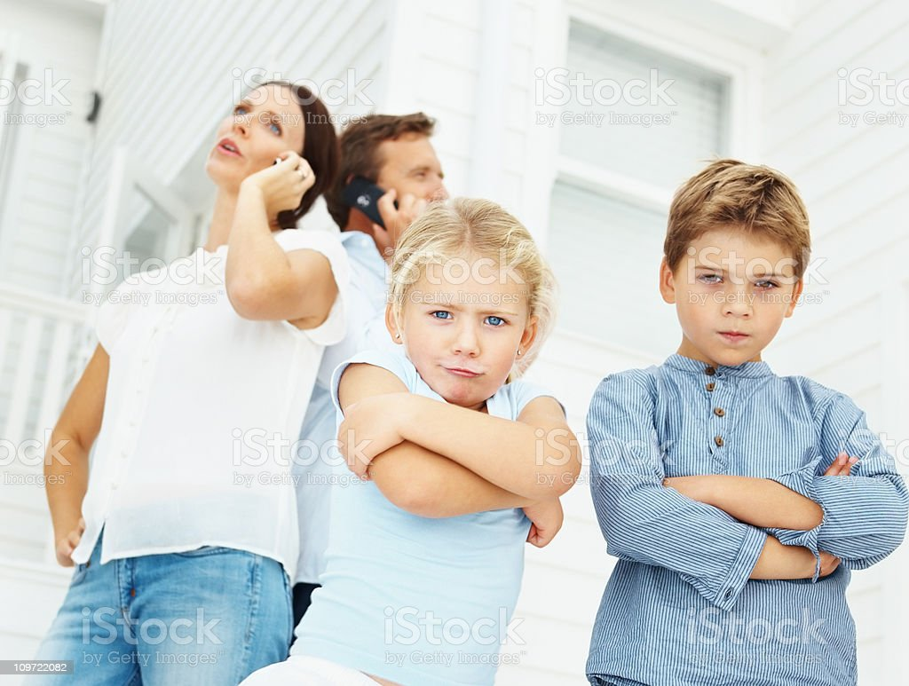 Children with parents talking on cellphone at the back royalty-free stock photo