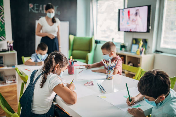 Children with protective face masks drawing in preschool