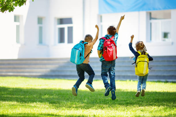 Children with rucksacks jumping in the park near school stock photo
