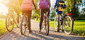 istock Children with rucksacks riding on bikes in the park near school 1301402437