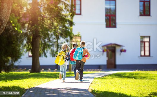 istock Children with rucksacks running in the park near school 802400188