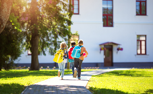 istock Children with rucksacks running in the park near school 802400188