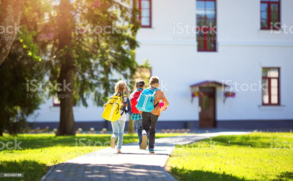 Children with rucksacks running in the park near school stock photo