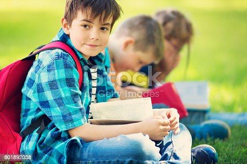 834369132 istock photo Children with rucksacks sitting in the park near school 801892038