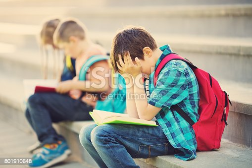 istock Children with rucksacks sitting on the stairs near school 801910648