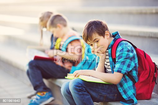 istock Children with rucksacks sitting on the stairs near school 801961640