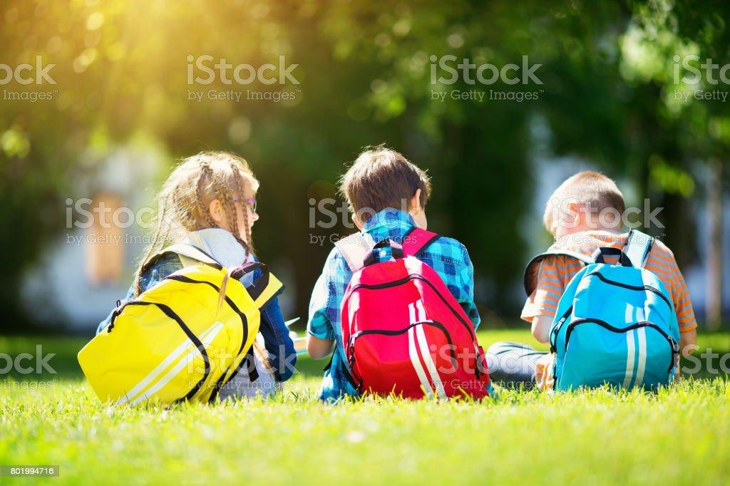 Children with rucksacks standing in the park near school stock photo