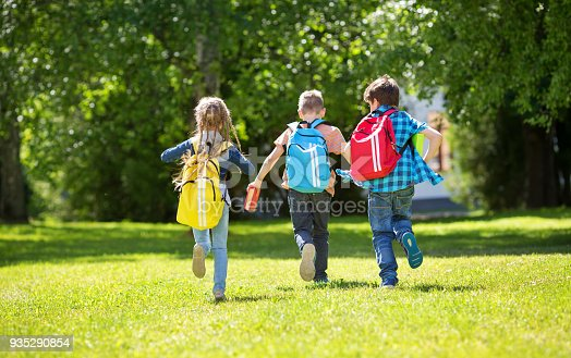 istock Children with rucksacks standing in the park near school 935290854