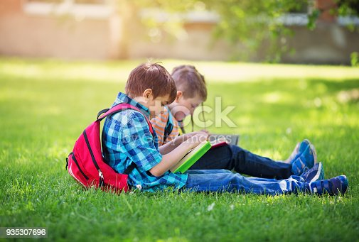834369132 istock photo Children with rucksacks standing in the park near school 935307696