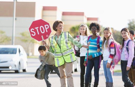 School crossing guard (Hispanic mature woman, 50s) helping children walk across street.