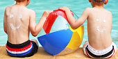 istock Children with Suntan Lotion Smileys on Backs at Swimming Pool 520713696