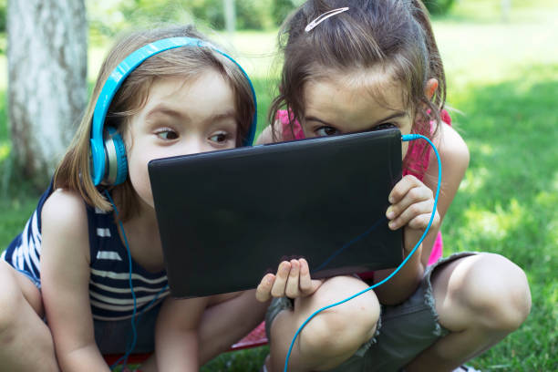 Children with tablet Two little children using tablet outside. digital native stock pictures, royalty-free photos & images