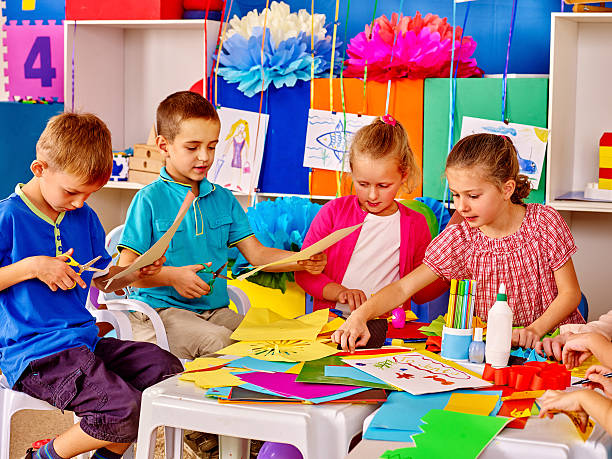 Children with teacher are making something out of colored paper. – Foto