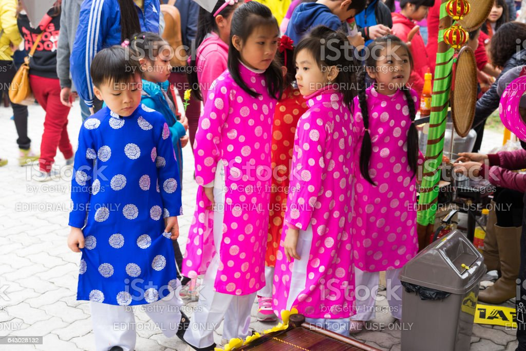 Hanoi, Vietnam - Feb 7, 2015: Children with Vietnamese traditional long dress Ao Dai playing at Vietnamese lunar new year festival organized at Vinschool, Vinhomes Times City, Minh Khai stock photo