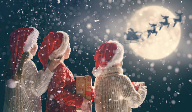 children with xmas presents Merry Christmas and happy holidays! Cute little children with xmas presents. Santa Claus flying in his sleigh against moon sky. Kids enjoying the holiday with gifts on dark background. sleigh stock pictures, royalty-free photos & images