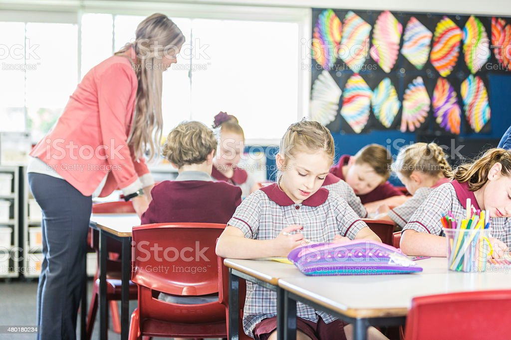 Children Working in Class While Being Supervised by their Teacher stock photo