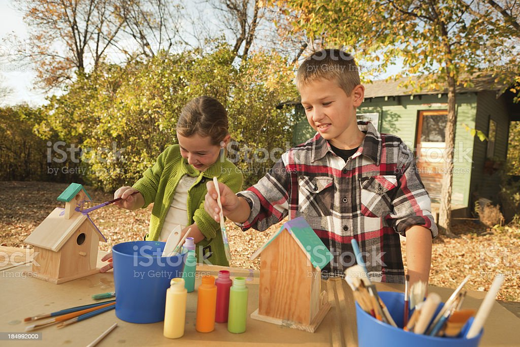 Children Working on Fun Project of Painting Birdhouse Hz royalty-free stock photo
