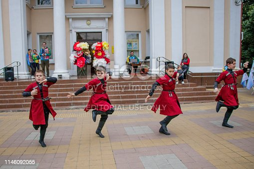 Sochi, Russia - 7 February, 2019: Children's group dances incendiary Caucasian dance in the city square of Sochi. Four boys in national costumes of red and black color act solo. In the background - stairs and entrance to the House of culture, decoration of flowers and a few people. The entrance to the Amateur concert is free, without tickets.